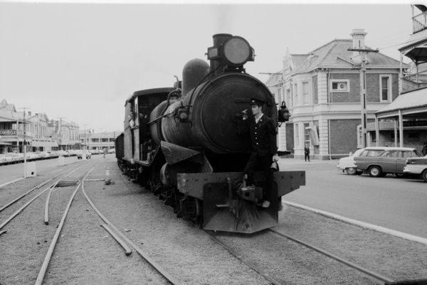A black and white image of the front of a black steam train with a conductor standing on the front guard. The train is running through a small town with cars parked to the side of the graveled road