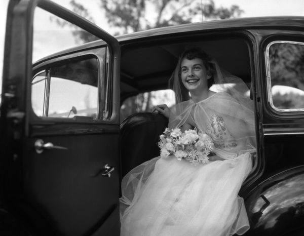 A black and white image of a bride dressed in wedding gown, holding a bouquet, getting out of a black vintage car. She is wearing a white veil and a shawl