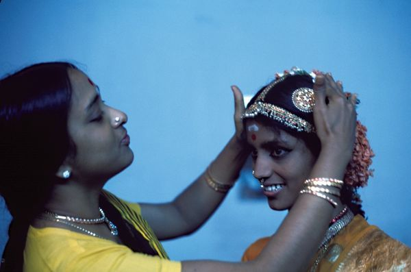An older woman fits a highly decorative headdress onto a young Hindu bride, who is smiling. This image is taken from 'Our Asian Neighbours - India' 1977, a 14-part series that takes a personal look at the lives of a variety of individuals in India