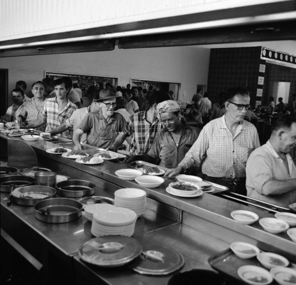 A black and white image of a group of men waiting in line to pick up their hot lunch, which is on the kitchen counter of their workplace canteen