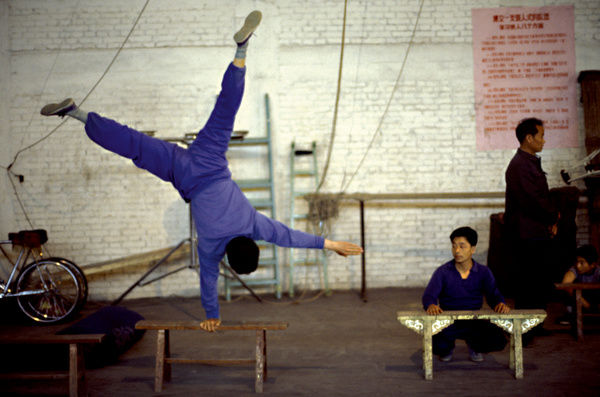 A colour image of a male acrobat wearing a blue shirt and trousers executes a one-arm handstand on a wooden stool. Another man is squatting down behind the acrobat, watching the technique as he leans on a similar wooden bench.Based in Xi?an
