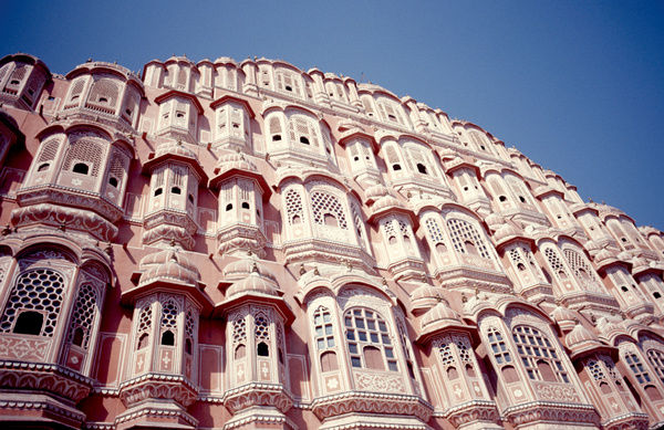 Looking up at the pink sandstone walls of the Hawa Mahal palace in Jaipur, India. An outstanding example of Mughal architecture, the palace was built in 1799 by Pratap Singh of Jaipur.  This image is taken from 'Anokhi': The story of John Singh