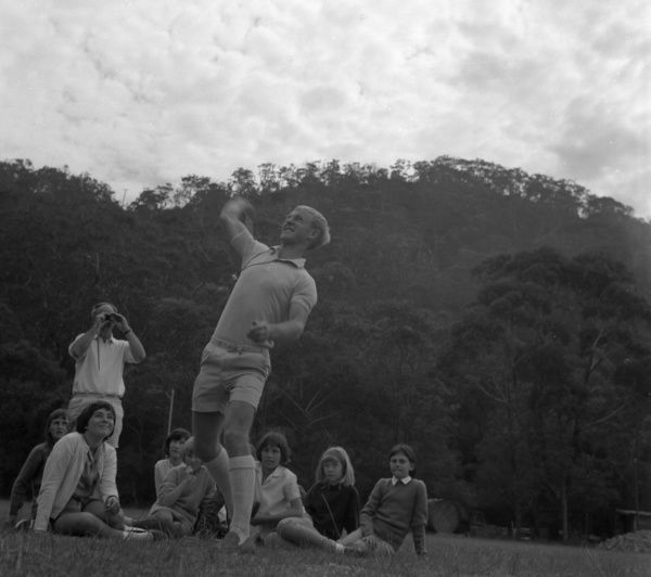 A black and white image of a group of children sitting on the grass in front of some mountain landforms. A young man is standing with one arm in the air, looking like he is mid throw. An older man is standing behind him, taking a photograph