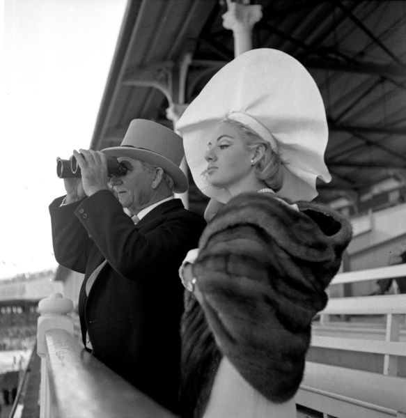 A black and white image of a man wearing a top hat standing with a woman wearing a large hat with a fur stole at horse racing event