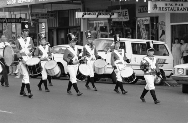 A black and white image of a marching band leading the 1987 Coo-ee Reenactment March through a town near Gilgandra, during the reenactment of the original Coo-ee march, where 26 men became 263 volunteer recruits which left Gilgandra on October 10