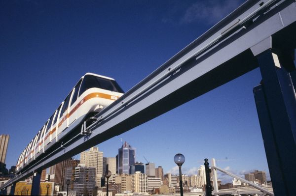 A colour image of the Sydney Monorail traveling over the Pyrmont Bridge in Pyrmont, Sydney. The Sydney city skyine cam be seen in the background of the image