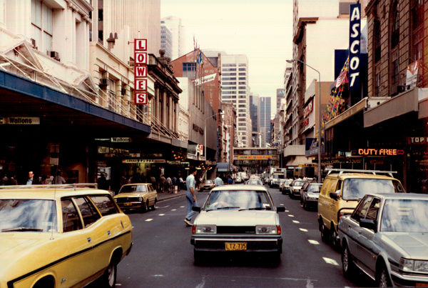 A colour image of Pitt Street, Sydney. The layout of the street has changed over the decades, as has the direction of the traffic. The image shows the now demolished Ascot Theatre and the old entrance to the Hilton hotel. Waltons department store