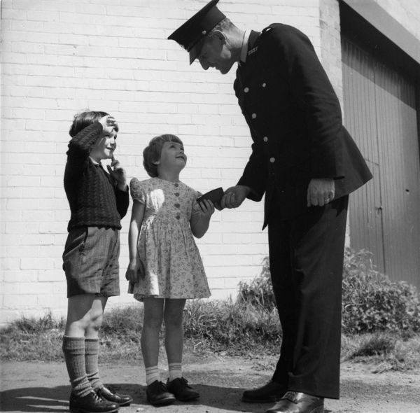 A black and white image of a young girl and boy giving a policeman a purse. The young girl hands the purse over to the policeman with a smile on her face as the young boy can be seen either shielding his face from the sun or saluting the serviceman