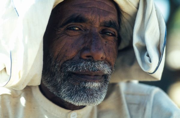 A close up portrait of a man in a loose white headdress, who wears a trimmed grey moustache and beard. This image is taken from 'Swami Shyan': A guru and his followers live in an ashram in Kulu Valley, which is part of the Himalayan region of India