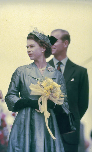 A colour photograph of Queen Elizabeth II and Prince Philip on their visit to Australia in 1954. The Queen is wearing a blue coat with black gloves and holds a bouquet of yellow flowers. Prince Phillip can be seen in the background