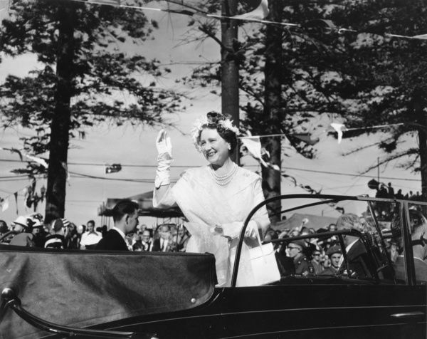 Queen Mother (Elizabeth Angela Marguerite Bowes-Lyon) waving to a crowd in Australia from the back of a black convertible in 1958