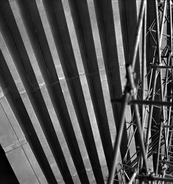 A black and white photograph of the construction of the Sydney Opera House. This photo features the details of the Sydney Opera House during construction. A steel structure is located to the right of the image. Construction was completed in 1973