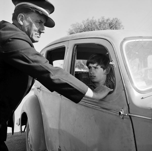 A black and white image of a young man sitting in the drivers side of a car, with a policeman leaning on the open window with his hands. L- R: Tom Burstall (Wayne), Frances Hattam (Carol), Tim Burstall (Director), Volk Mol (Cinematographer)