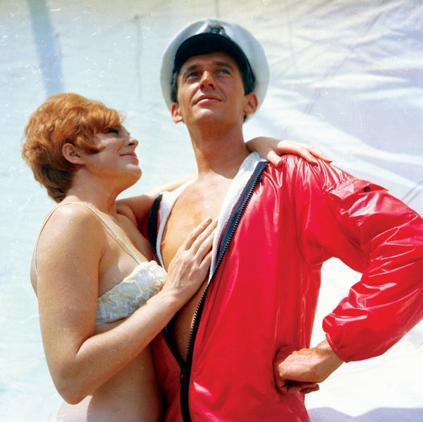 A woman with short, red hair and dressed in a white, lacy bikini gazes adoringly up at a man wearing a captain's peaked cap and a red, shiny wet weather jacket, which is open to expose his chest and torso. In the background is white sailcloth