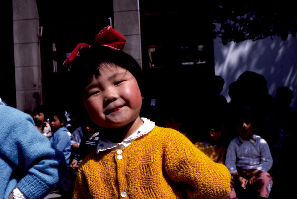 A close up, colour portrait of a young Chinese girl dressed in a yellow knit cardigan with a red bow in her hair, smiling directly into the camera