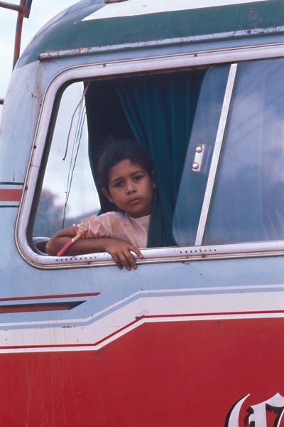 A colour image of a young girl looks out the window of a bus