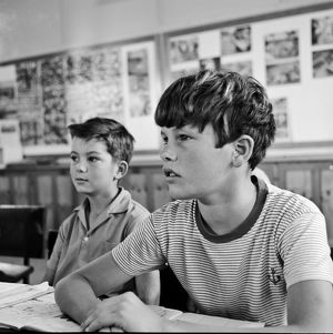 Black and white image of two boys at their desks in a classroom.
