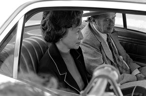 A couple of American tourists sit in the back seat of a small car.