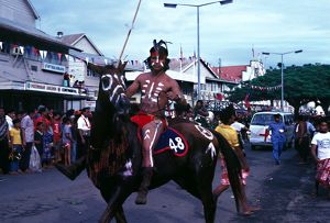A man in ceremonial dress rides a horse along the street.