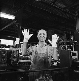 A man wearing overalls in a factory holds up his bandaged hands.