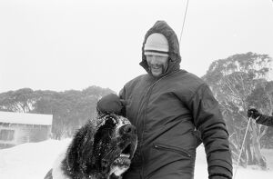 A man weating ski clothes pats a Saint Bernard dog in the snow.