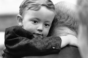 A young boy with his arms wrapped around an old man's neck.