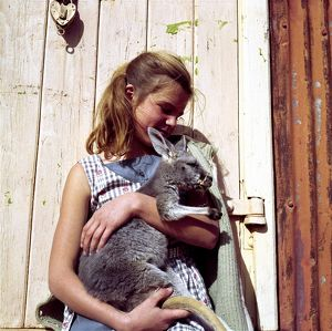 A young Caucasian girl cuddles a joey in front of a wooden door.
