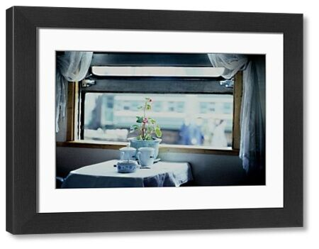 A small laid table under an open window looking out onto an urban landscape. On the table are some blue and white crockery and a flowering potplant