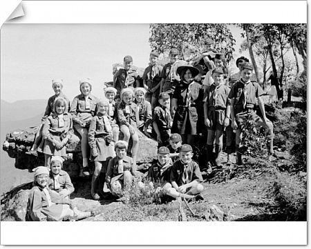 A black and white image of scouts and brownies standing for a group portrait on a rocky ledge. The children are dressed in their guides uniforms, including hats and cravat