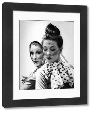 A black and white close-up portrait of two female actors in theatrical cat makeup