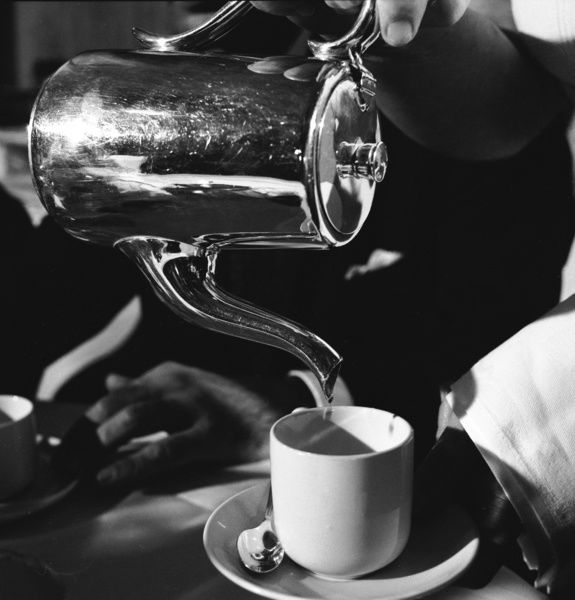 A black and white image of a closeup of a hand pouring liquid into a white cup and saucer from a silver coloured pot