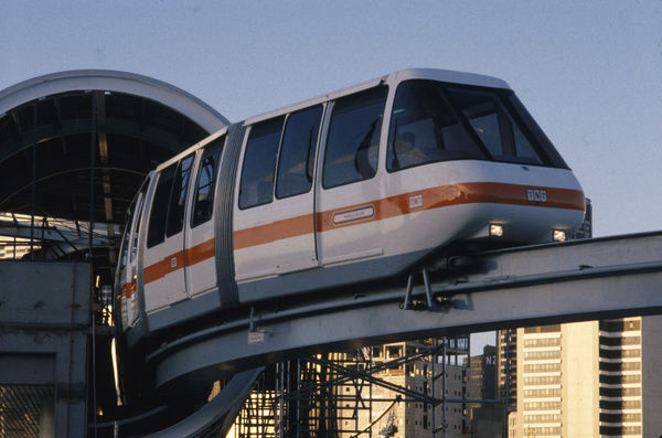 A colour image of the now demolished Sydney Monorail carriage coming out of the station stop. Some of the Sydney city buildings can be seen in the background of the image as the sun reflects of them
