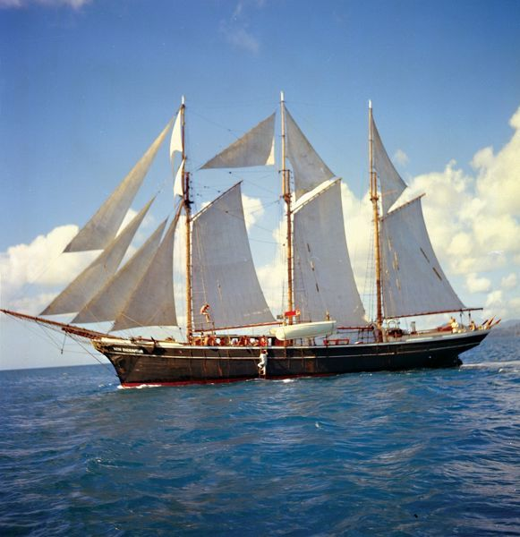 A colour image of the sailing New Endeavour with film crew on board. The sails have have been deployed as the boat sails past a grouping of clouds