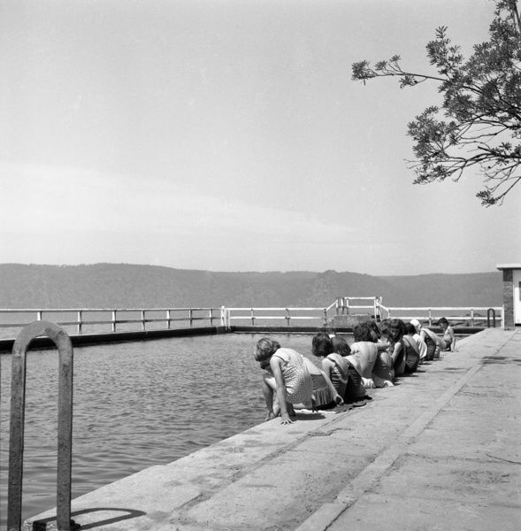 A black and white image of a group of children sitting on the side of a sea pool on Pittwater, having a swimming lesson