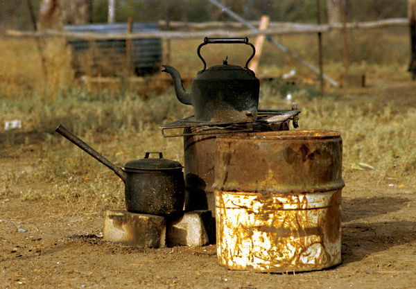 A colour image of a small pot and a kettle resting on bricks as they are being heated by a small fire. A large barrel drum is placed next to the items. The surrounding area is grassland with a wire fence and water barrel in the background