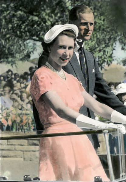 A photograph from the Australian Royal tour in 1954. Queen Elizabeth II and Prince Philip can be seen standing on the back of a moving vehicle. The Queen accessorizes her outfit with gloves, a string of pearls and a hat