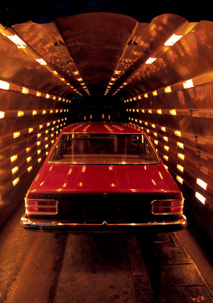 A colour image of a red car in a brightly lit tunnel. The light reflects off the car, creating small, rectangle white spots on the painted exterior