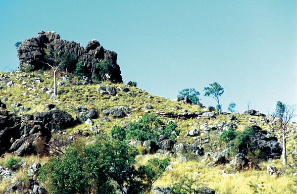 A colour image of a large rocky outcrop on top of a scrubby hill in Western Australia