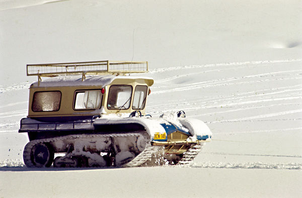 A colour image of a snow vehicle known as a snowcat crossing over an expansive snowy area. A slope can be seen in the background of the image