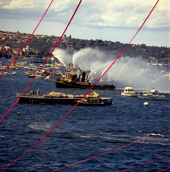A colour image of ferries, naval ships and various water vessels on the harbour, for the Sydney Opera House opening ceremony in 1973. The Kirribilli shoreline can be seen in the background of the image