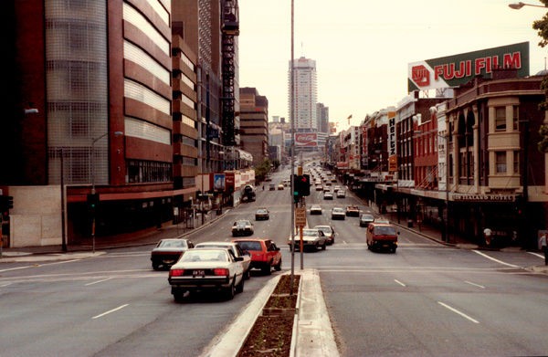 A colour image of a four lane road in Sydney, Australia. The image is of William Street in Sydney facing Kings Cross. Yurong Street can be seen to the right of the image, with the New England Hotel ( Now Hotel William) on the corner of the street