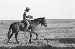 B&W image of a male jackeroo riding a horse in the desert