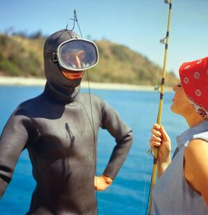marine/man wetsuit hooked woman carrying fishing rod