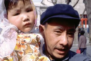 people/portrait chinese man blue cap holding young girl
