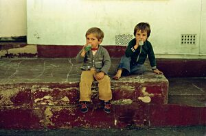 Two young boys sit on a front doorstep, drinking from bottles.