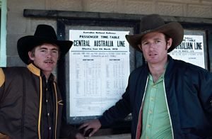 people/young men cowboy hats pose train timetable